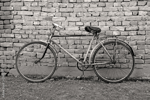 Fototapeta old bicycle leaning against a wall