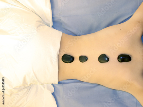 spa: a girl takes a hot stones massage