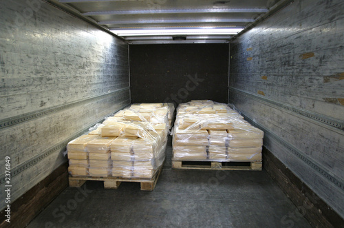 manufactured cheese on pallets in back of truck - 2376849