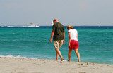 retired couple waling on beach poster