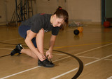 teen girl in gymnasium ties shoes poster