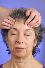 massaging head of senior woman at spa