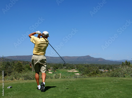golfer driving golf ball on beautiful golf course
