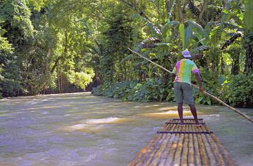 man on river raft jamaica