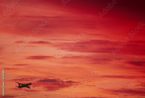 jetliner flying into red sunset