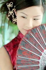 asian girl in red chinese dress holding a fan
