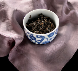 cup of dried tea on lavender silk