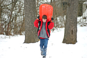 boy carrying sled