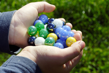child holding two hands full of marbles