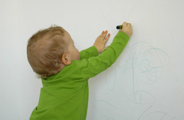 little child drawing on the wall