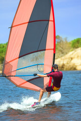man in wetsuit on fastmoving windsurfer