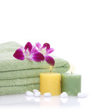 green towel, orchid, candles and pebbles