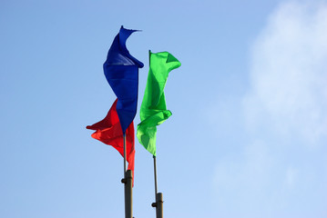 three colour flags waving and clouds