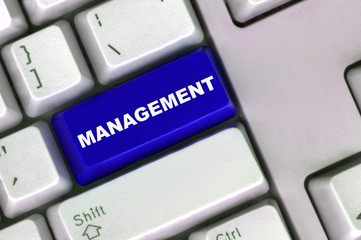 keyboard with blue button and word of management
