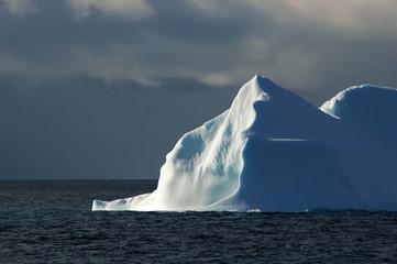 sunlit white-blue iceberg with dark sky