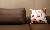floral pillow on a brown leather couch poster