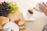 pouring a cup of herbal tea next to a cheese board poster