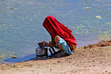 india, rajasthan, thar desert: woman searching water in a very p