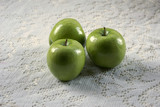 three granny smith apples on lace poster