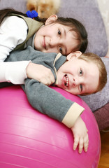 two happy children on the big red ball