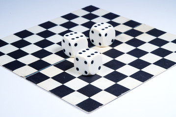 3 dice on a chess-board, isolated on a white background