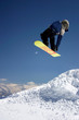 snowboarder in blue jacket jumping high - winter mountain action