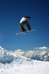 snowboarder jumping high - a winter mountains action scene
