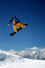 snowboarder in orange jumping high - winter mountains action sce