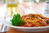 spaghetti with a tomato sauce on a table in cafe poster