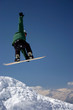 snowboarder in green jacket juping high - winter mountain action