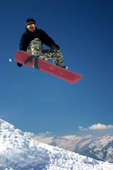snowboarder in moro desert pants jumping high - winter mountain