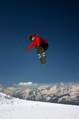 snowboarder in red jacket jumping high - winter mountains action