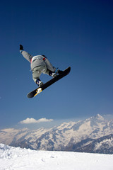 snowboarder in grey jacket juping high - winter mountain action