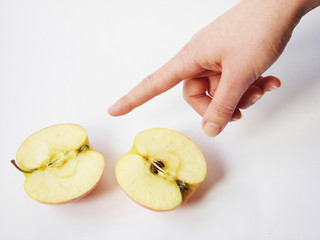 a female hand pointing at a cut apple