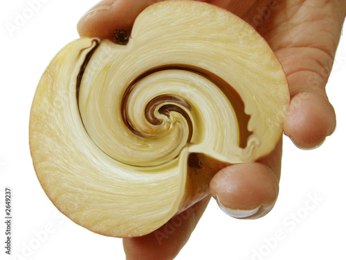 a female hand holding a cut twisted apple