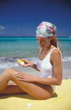 donna si mette la crema al mare poster