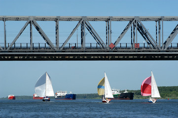yachts and float sea vessels under the bridge on the river don