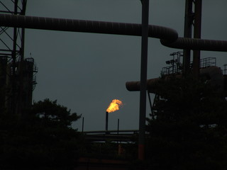 flaming stack of pollution from an industrial park