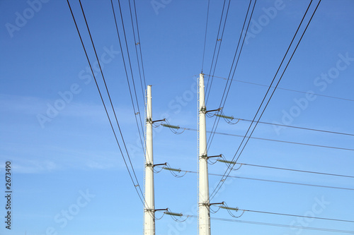 two white electricity pylons and stretching wires
