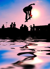 skateboarder jumping over the water at sunset