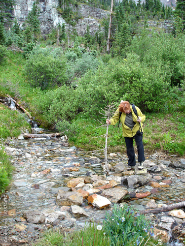 hiker crossing stream with stick