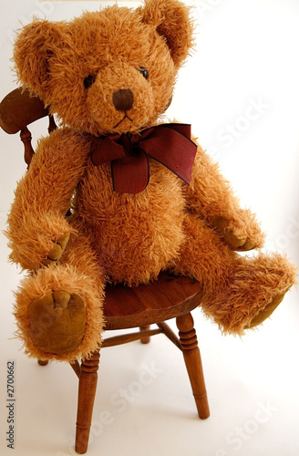 Leinwanddruck Bild teddy bear sitting on a chair