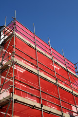 a building covered in scaffolding and red tarpauli