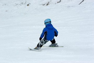 a boy downhill skiing
