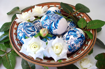 beautiful blue easter eggs with flowers in a dish over white bac