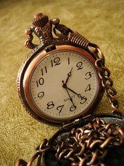 close-up of old golden clock on vintage background