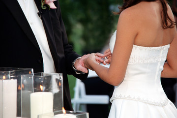 close up bride placing ring on groom