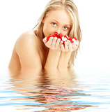 Fototapety blond with red and white rose petals in water