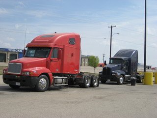 red freightliner truck and black kenworth truck