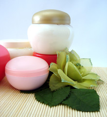 containers of cosmetic moisturizing cream with green flower